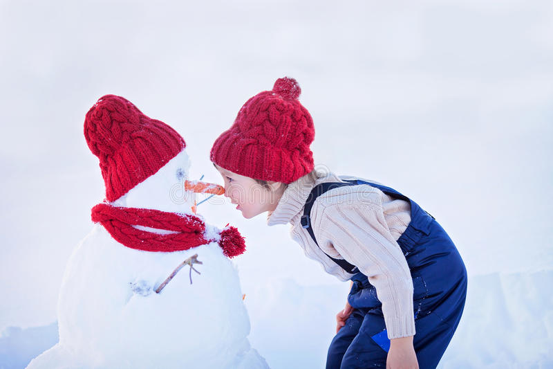 Bonhomme de neige heureux de bâtiment de bel enfant dans le jardin, hiver, nez t photo stock