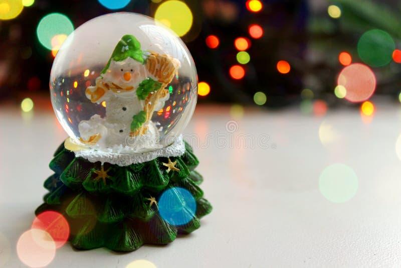 Bonhomme de neige de jouet de Noël dans la boule sur le fond clair, effet de bokeh, image libre de droits