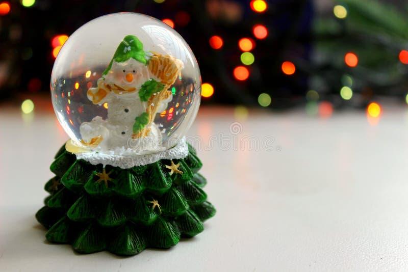Bonhomme de neige de jouet de Noël dans la boule sur le fond clair, effet de bokeh, photos libres de droits