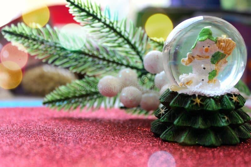 Bonhomme de neige de jouet de Noël dans une boule sur un fond rouge image stock