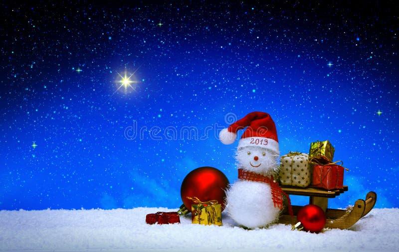 Bonhomme de neige de Noël avec le chapeau du père noël d'isolement sur le fond de ciel d'étoile photo stock