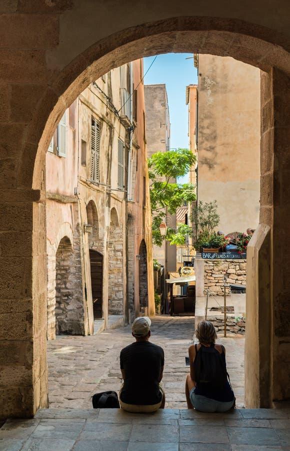 """BONIFACIO KORSIKA †""""SEPTEMBER 30 2018: Två mogna mellersta åldriga turister tar skyddet från den varma middagsolen arkivfoto"""