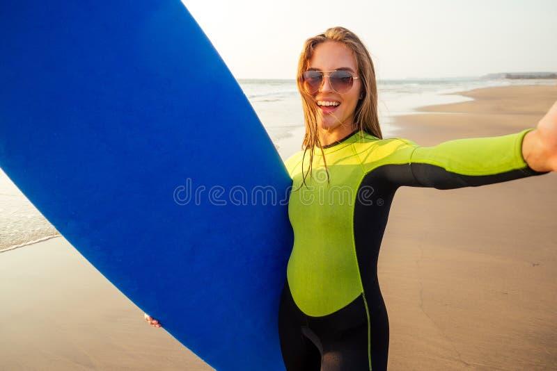 Bonita e sorridente surfista em um traje de mergulho, segurando surfboard e fotografando um retrato selfie fotografia de stock