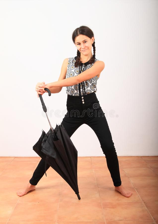 Bonita garota de roupas na escola com guarda-chuva preto foto de stock