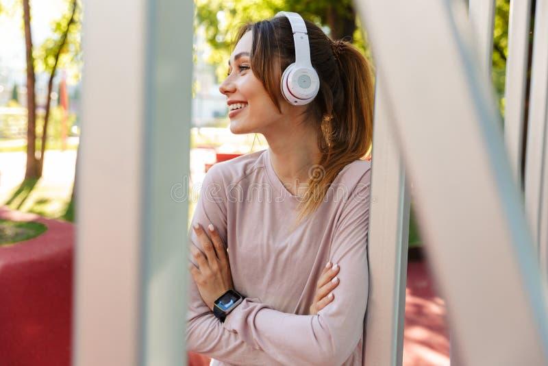 Bonita jovem e alegre atriz desportiva a posar ao ar livre no parque ouvindo música com fones de ouvido imagem de stock royalty free