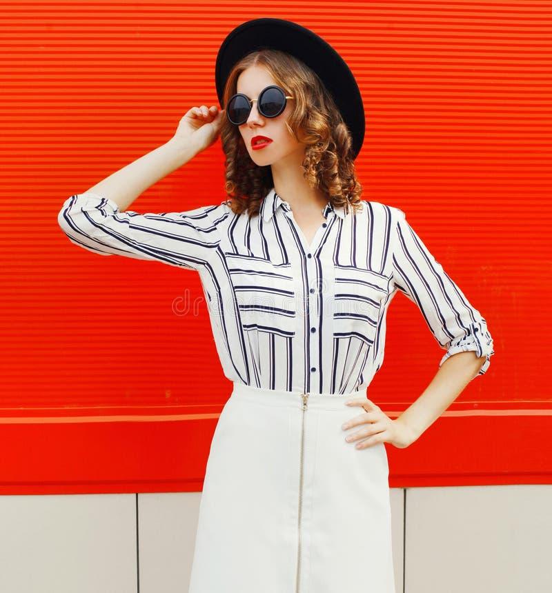 Bonita jovem modelo usando camisa listrada branca, chapéu redondo preto na rua da cidade sobre a parede vermelha fotos de stock royalty free