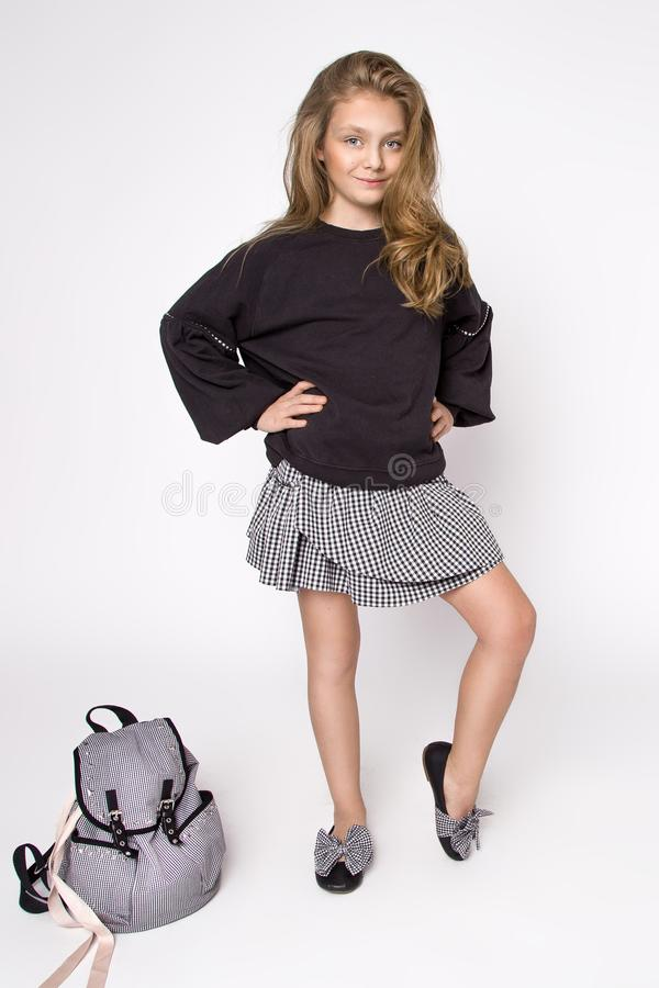 Bonita, a menina vestiu-se na roupa da escola e na trouxa da escola, poses no estúdio De volta à escola fotografia de stock royalty free