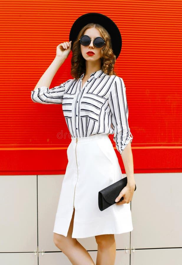 Bonita moça modelo usando camisa listrada branca, embraiagem preta, chapéu redondo, saia na rua da cidade sobre a parede vermelha foto de stock