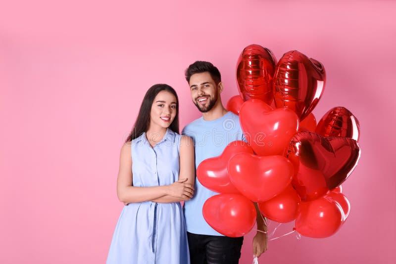 Bonita pareja con globos en forma de corazón en segundo plano Celebración de San Valentín fotografía de archivo libre de regalías