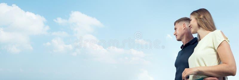 Bonita pareja joven en el cielo azul Cartel fotos de archivo libres de regalías