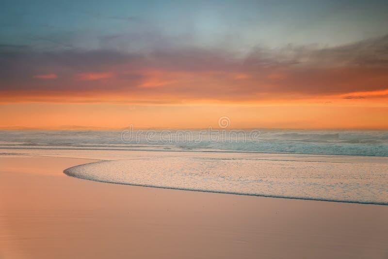 Bonita puesta de sol en la playa con una ola fotografía de archivo libre de regalías