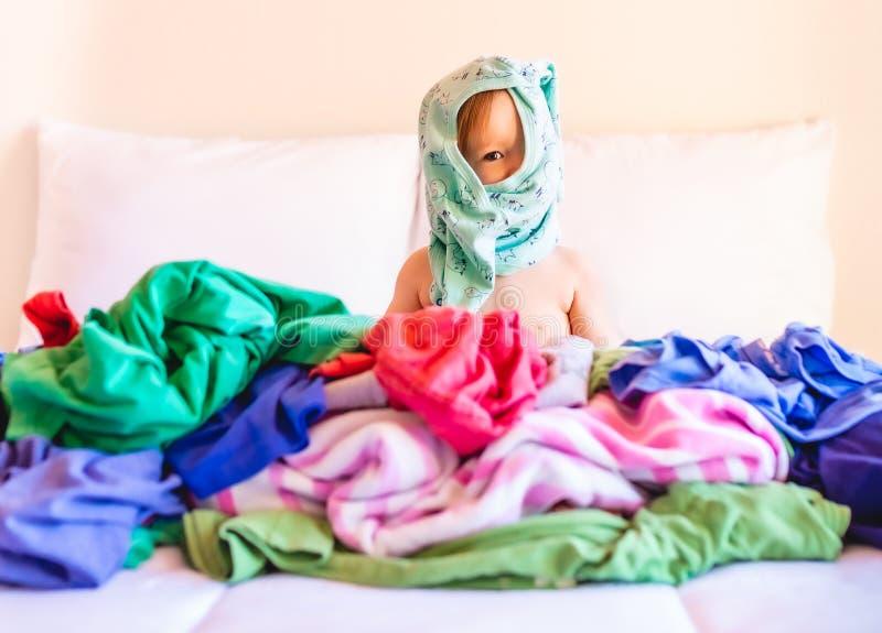 Bonito, ador?vel, sorrindo, beb? caucasiano que senta-se em uma pilha da lavanderia suja na cama fotografia de stock