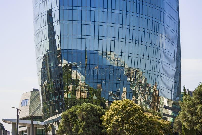 Bonito, arranha-céus, construções elegantes que estão em uma montanha alta Reflexão da cidade e do mar nas janelas de vidro imagens de stock