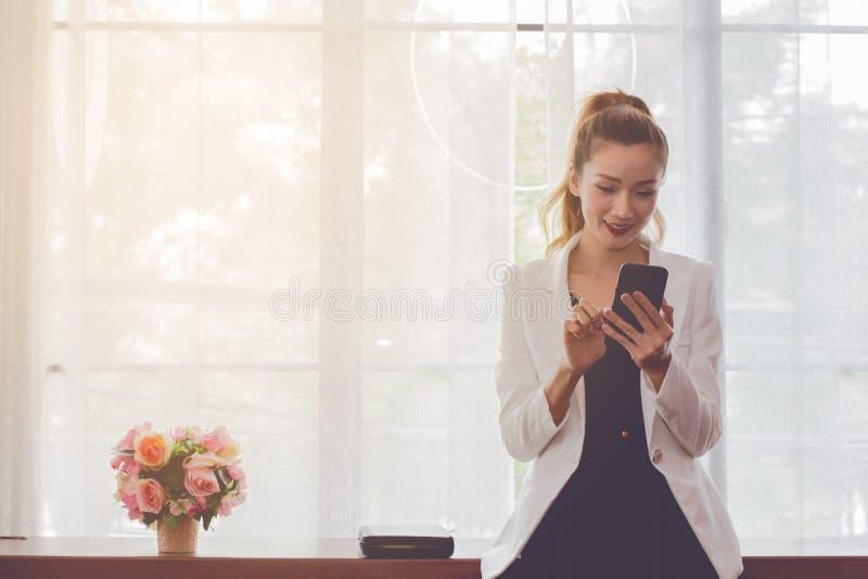 Bonito asiático no vestido branco com a mulher de negócios marrom longa do cabelo que usa a partida esperta do telefone está dese fotografia de stock