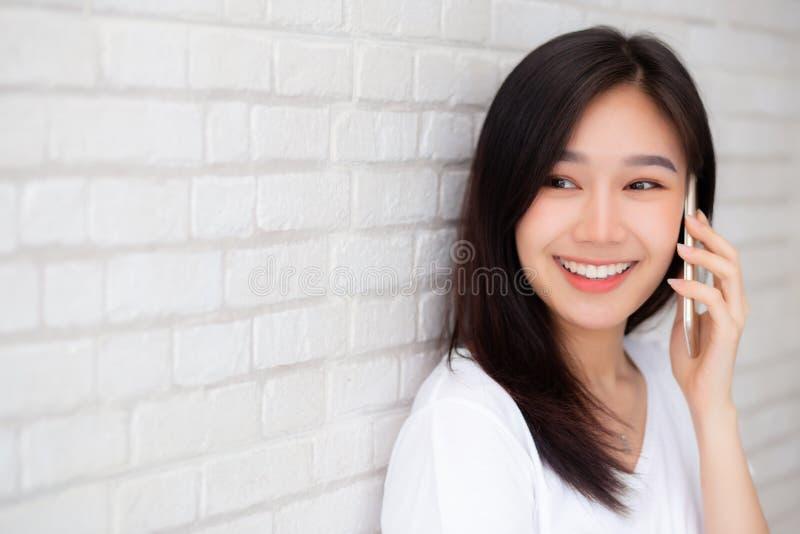 Bonito da conversa asiática nova da mulher do retrato do telefone esperto e do sorriso que estão no fundo do tijolo do cimento fotografia de stock