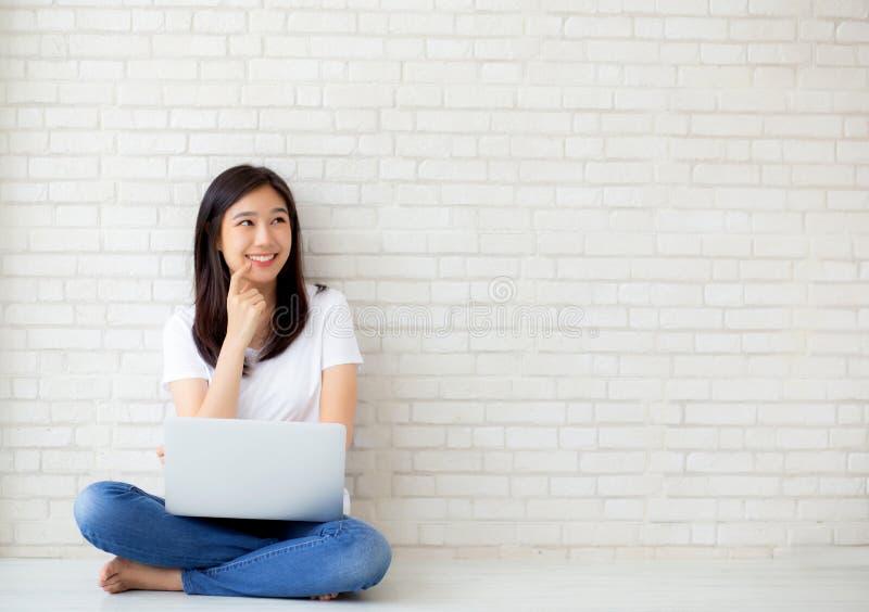 Bonito da jovem mulher asiática do retrato que trabalha o portátil em linha e que pensa o assento no fundo do cimento do tijolo d fotografia de stock royalty free