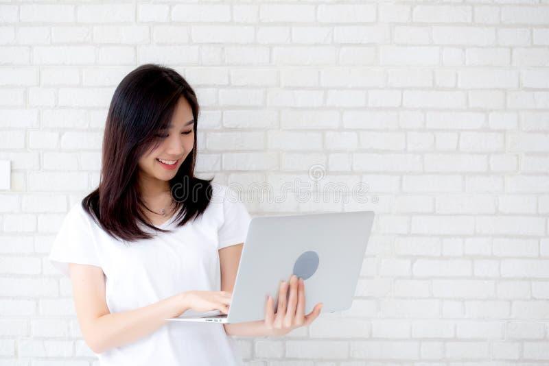 Bonito da mulher asiática nova do retrato que sorri e que está guardando o portátil no fundo da parede do cimento do tijolo imagem de stock