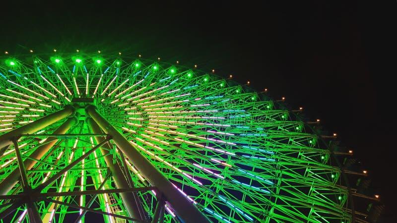Bonito disparou em uma roda de ferris na noite com lasers verdes imagem de stock