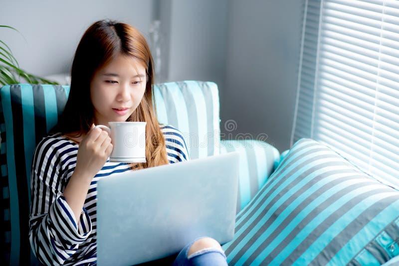 Bonito do cartão de crédito asiático novo do uso do assento da mulher do retrato com portátil e café da bebida imagens de stock