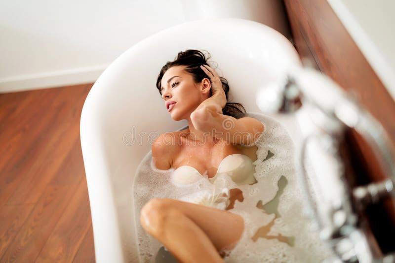 Bonito e jovem mulher que apreciam o tempo na banheira foto de stock royalty free