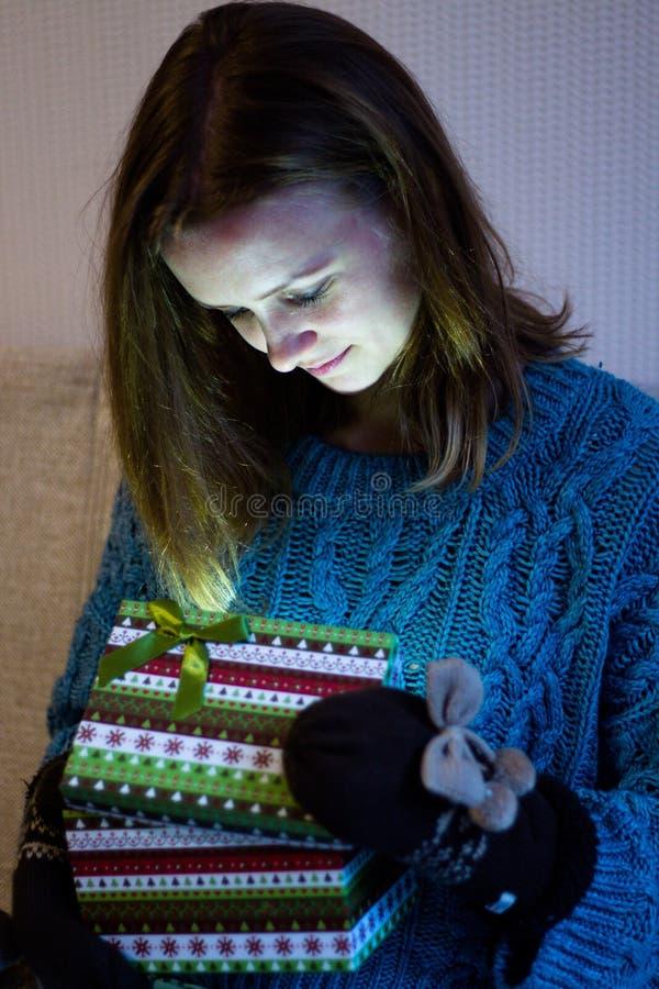 Bonito e moça abre uma caixa com testes padrões modernos em que um presente brilhantemente ardente fotografia de stock