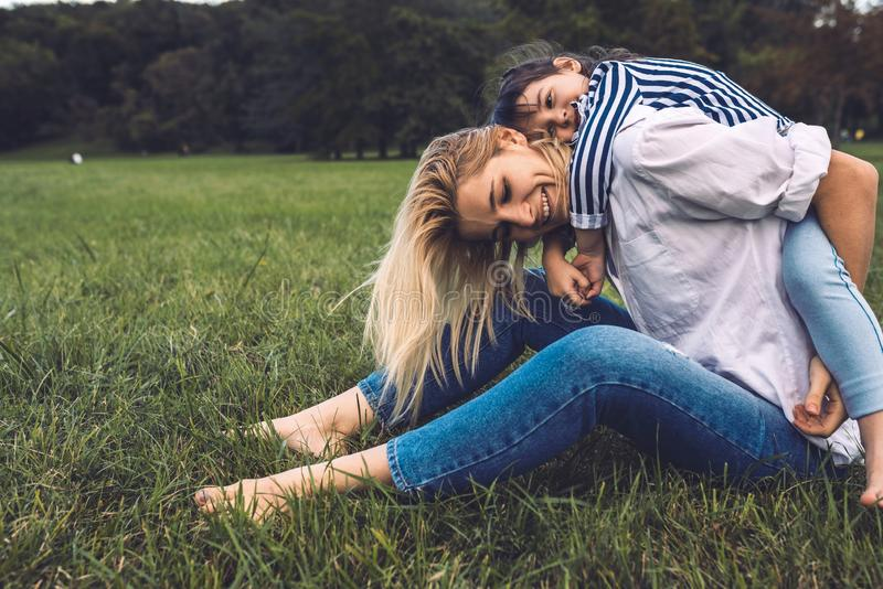 Bonito feliz pouca filha em um passeio do reboque com sua mãe Mulher de sorriso de amor e sua menina que sentam-se na grama verde imagens de stock