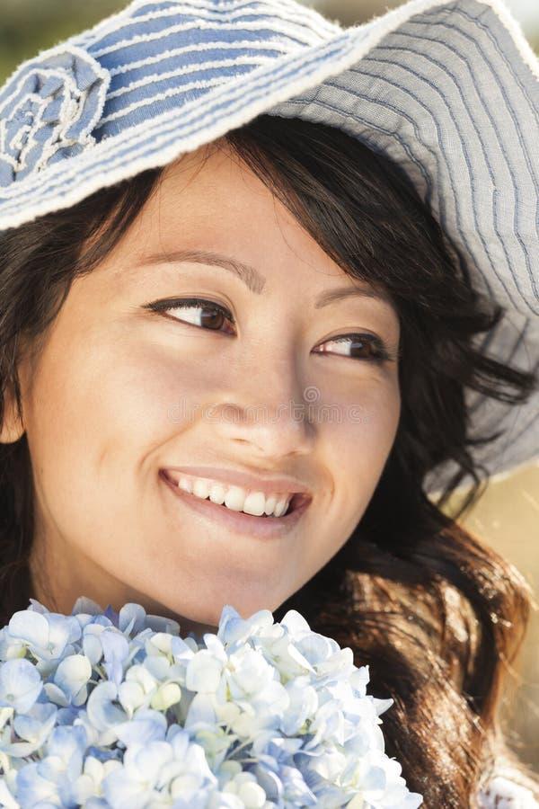 Bonito, feliz, saudável, sorrindo, mulher asiática nova com ar livre macio, liso, sem falhas da pele no verão Está guardando fres fotografia de stock royalty free