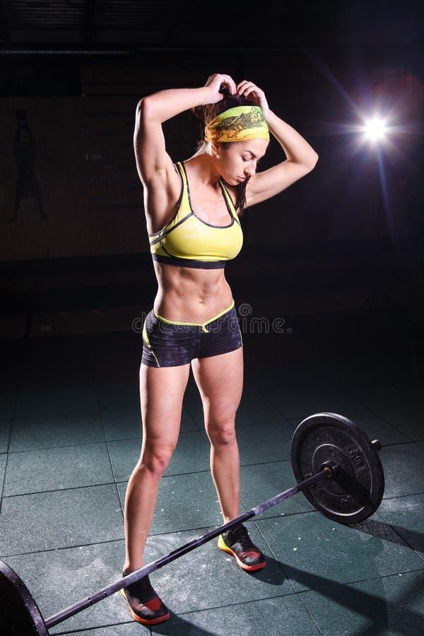 Bonito, forte, delgado, na boa forma física no gym que faz exercícios Vestido no short curto e no verde da camiseta de alças, no foto de stock royalty free