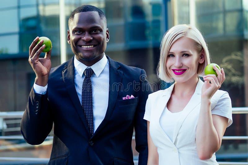 Bonito hombre de negocios africano con un elegante traje negro con una atractiva mujer de negocios rubia comiendo una manzana verd imagenes de archivo