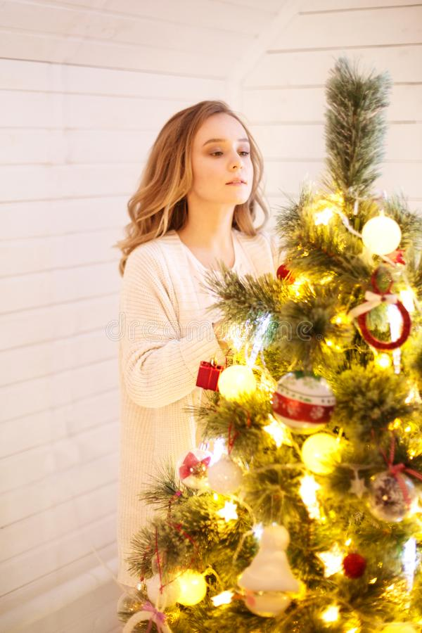 Bonito, jovem mulher que decora uma árvore de Natal imagens de stock royalty free