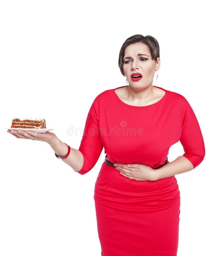 Bonito mais a mulher do tamanho com dor em sua barriga isolada imagem de stock