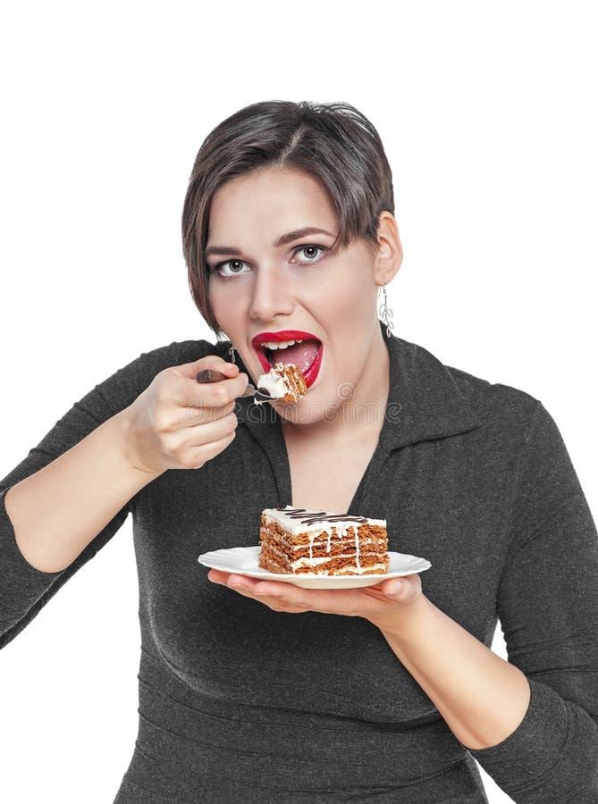 Bonito mais a mulher do tamanho que come o bolo isolado foto de stock royalty free