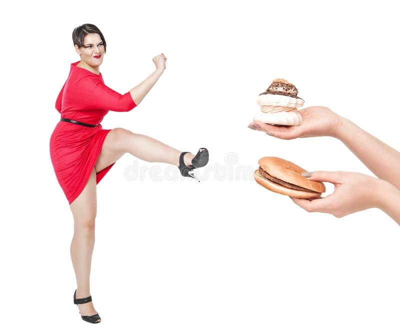 Bonito mais a mulher do tamanho que luta fora o alimento insalubre isolado fotos de stock