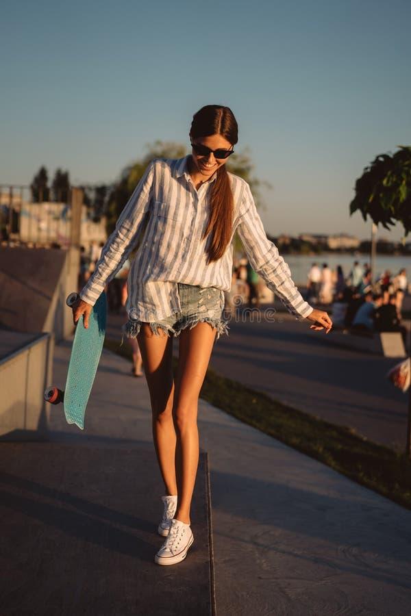 Bonito, moça com um skate no parque do patim fotos de stock