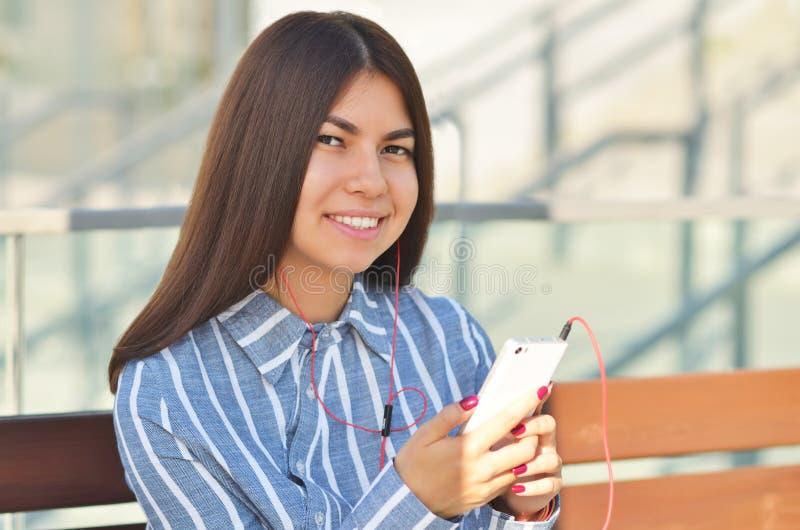 Bonito novo é sitts asiáticos da menina no banco e escuta a música imagem de stock