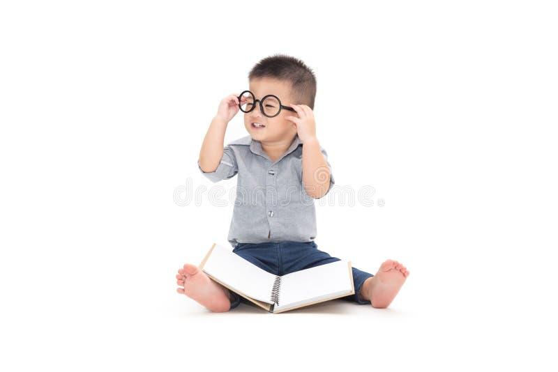 Bonito pouca brincadeira com livro e vidros vestindo ao sentar-se no assoalho isolado sobre o fundo branco, fotos de stock royalty free