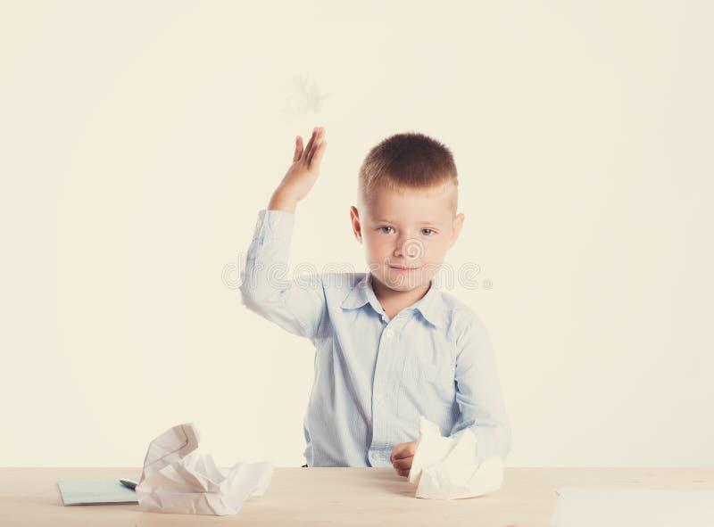 Bonito pouco menino de escola com o sorriso enorme que senta-se em sua mesa no fundo branco joga um pedaço de papel fotos de stock royalty free