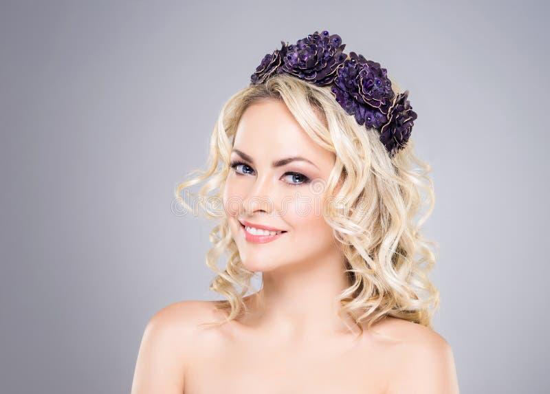 Bonito, sorrindo, bijouterie vestindo da jovem senhora sobre o fundo cinzento fotografia de stock royalty free
