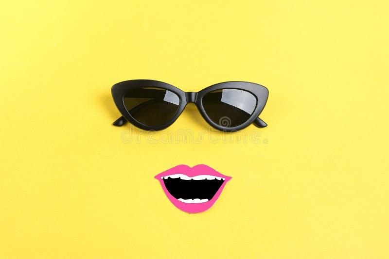 Bonjour été le soleil avec les lunettes de soleil noires élégantes, bouche de sourire sur le fond jaune images libres de droits