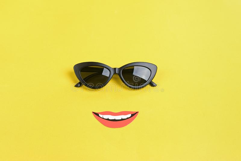Bonjour été le soleil avec les lunettes de soleil noires élégantes, bouche de sourire sur le fond jaune photo libre de droits