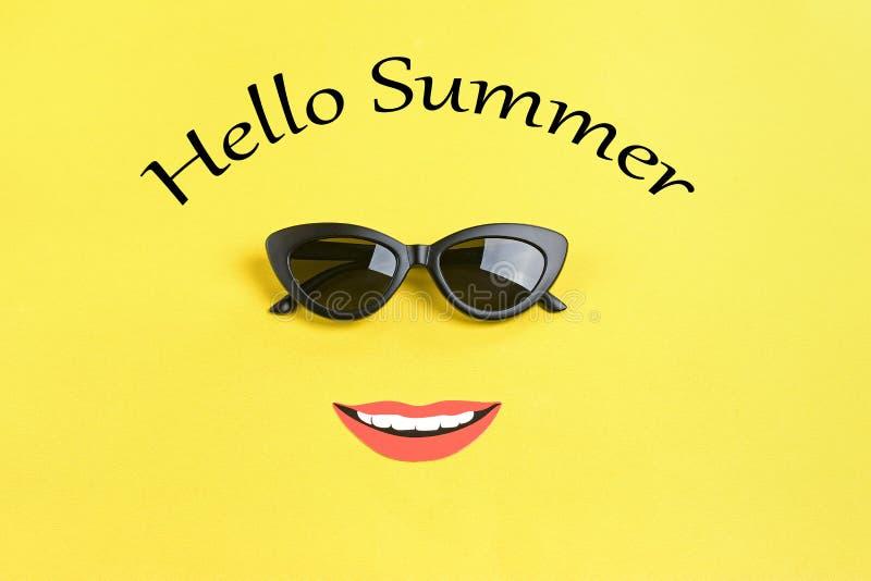 Bonjour été le soleil avec les lunettes de soleil noires élégantes, bouche de sourire sur le fond jaune photos stock