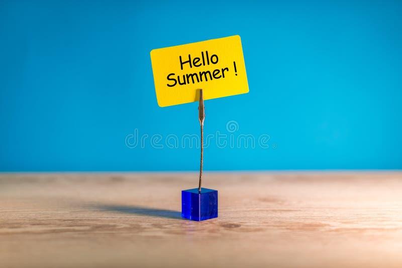 Bonjour été - textotez sur une petite étiquette jaune sur le fond lumineux bleu Premier jour d'été Le jour des enfants heureux image stock