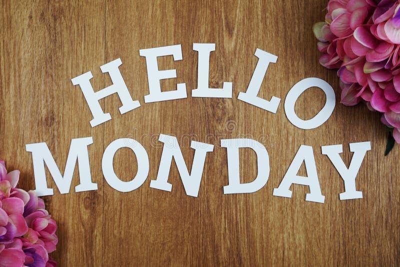 Bonjour alphabet en bois de lettre de lundi avec la fleur sur le fond en bois photo libre de droits