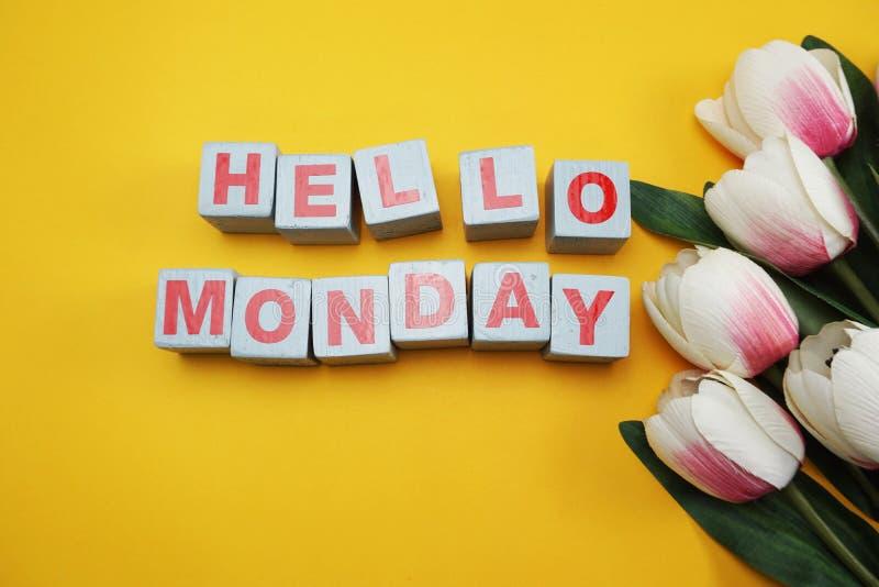 Bonjour alphabet en bois de lettre de lundi avec la fleur de tulipe sur le fond jaune images libres de droits