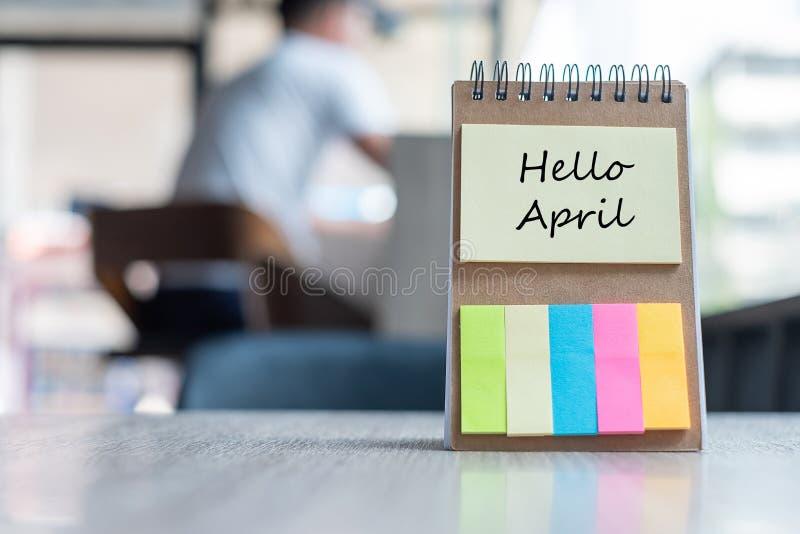 Bonjour avril avec le calibre de rappel de papier de note avec le stylo sur la table en bois copiez l'espace pour votre texte photos libres de droits
