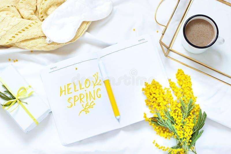 Bonjour composition étendue plate en ressort avec des fleurs de mimosa, une tasse de café et un cadeau photos stock