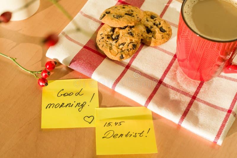 BONJOUR, DENTISTE sur la table à la maison Fond - nappe avec une tasse de café et de biscuits photographie stock libre de droits