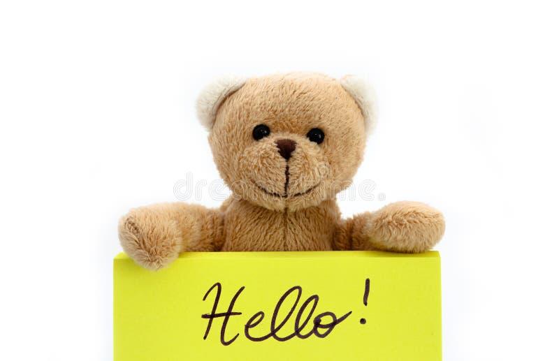 Bonjour, dit l'ours de nounours : ours de nounours brun tenant une note dans la couleur jaune lumineuse avec le message manuscrit images stock