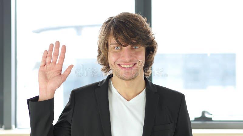 Bonjour geste par l'homme d'affaires occasionnel In His Office photo stock