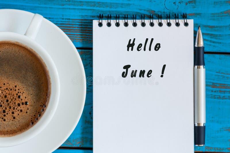 Bonjour juin - premier mois d'été Textotez au bloc-notes près de la tasse de matin de café image libre de droits